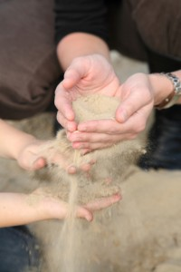hands-of-adult-and-child-with-sand